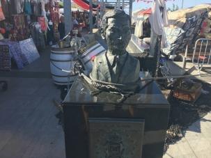 El busto de Adolfo Suárez en Liencres sostiene con cuerdas el puesto de un mercadillo
